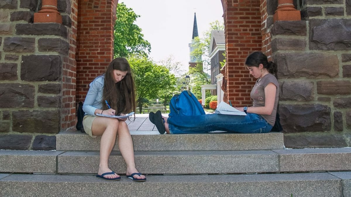 Two students reading and writing outside